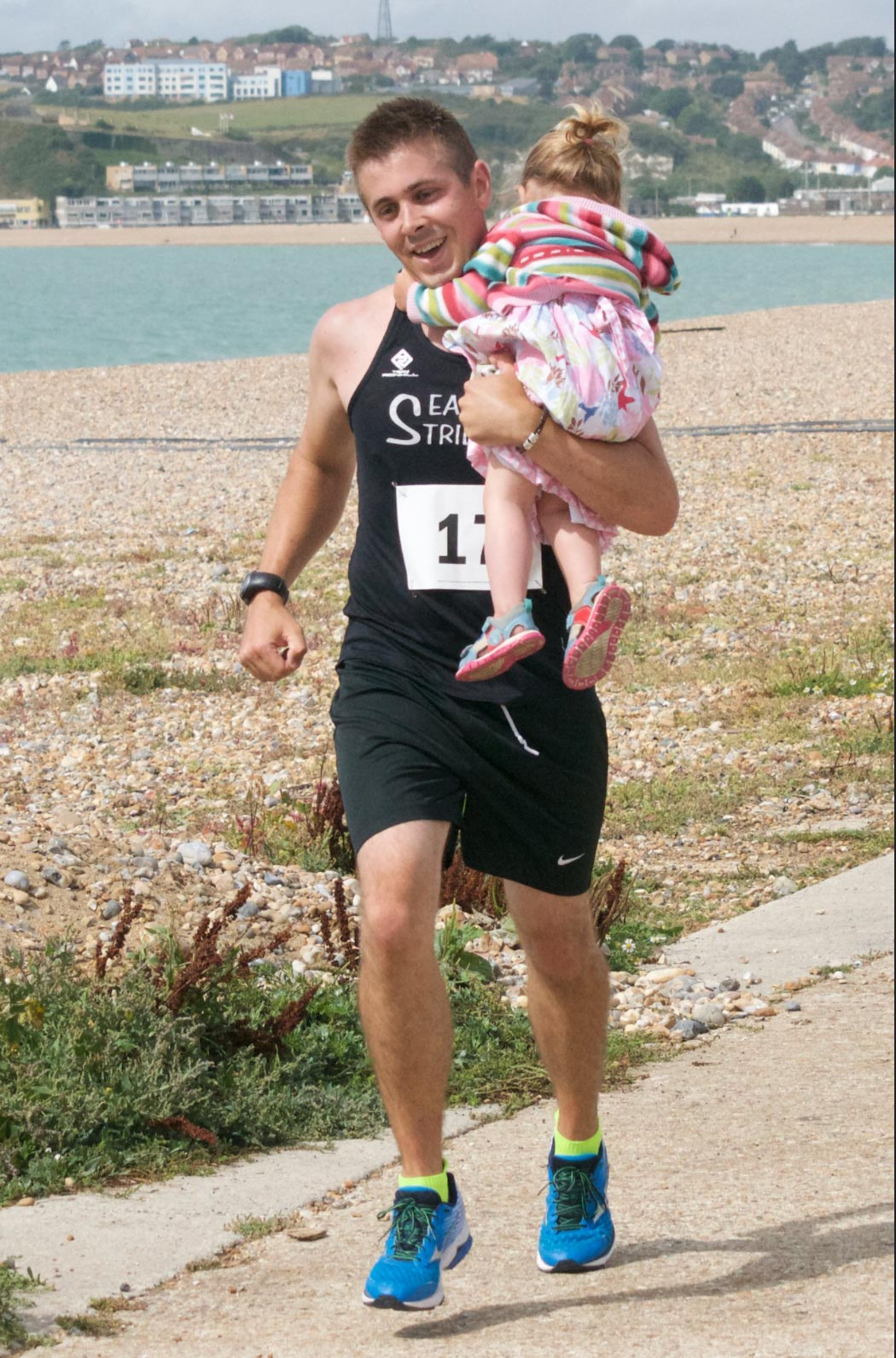 Runner carrying child in the Striders 30th Anniversary Run
