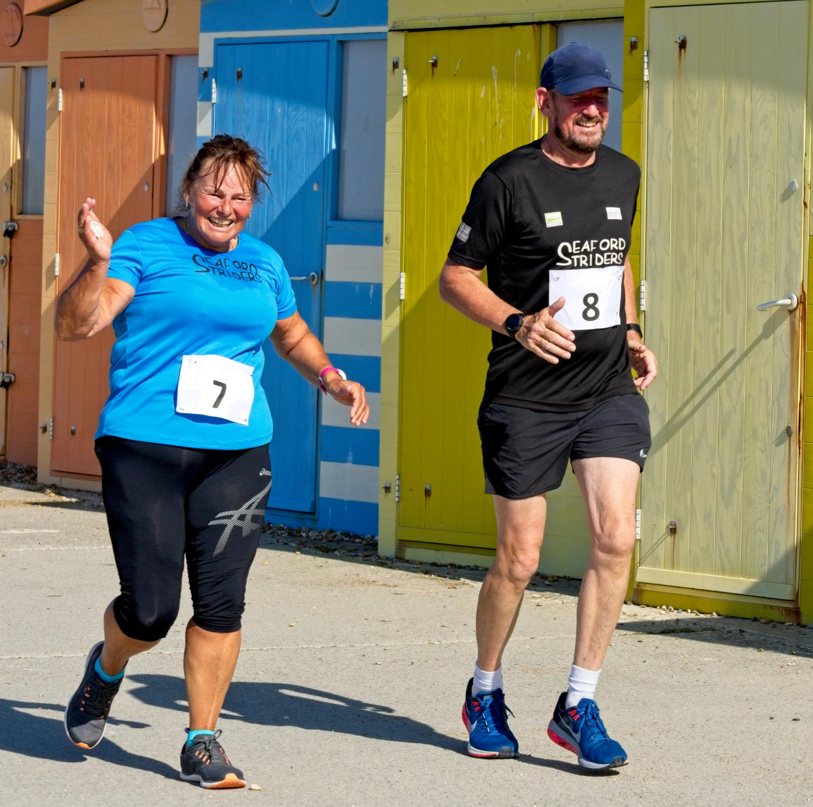 Man and woman running 10K run along Seaford Seafront